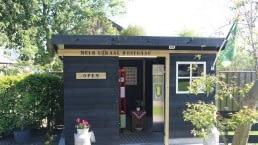 zwart houten gebouw met daar in een melktap en een automaat met kaas en eieren bij Melk Lokaal Westgaag in Midden-Delfland