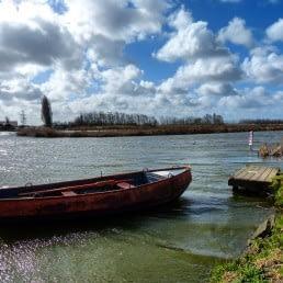 Bootje op het water met wolkenveld